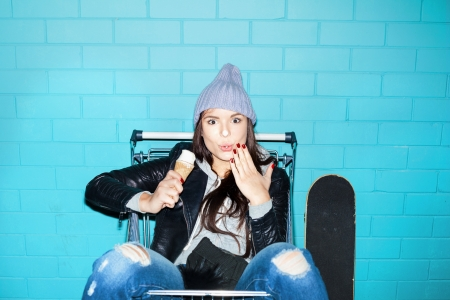 Young hooligan hipster woman eating ice cream over blue brick wall. Naughty girl having fun in shopping cart. Indoors, lifestyle photo