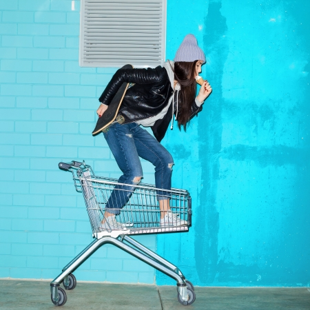 lifestyle shopping: Young funky woman with ice cream and skateboard standing in shopping cart over blue brick wall. Naughty girl having fun . Indoors, lifestyle Stock Photo