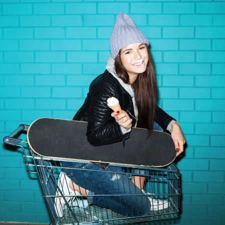 Young funky hipster woman nose smeared in shopping cart over blue brick wall. Naughty girl having fun . Indoors, lifestyle photo