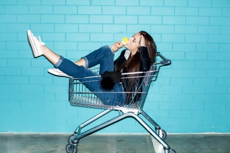 Young pretty woman eating ice cream over blue brick wall. Naughty girl having fun in shopping cart. Indoors, lifestyle