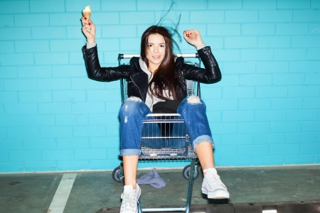 Young beautiful woman holding ice cream over blue brick wall. Naughty girl having fun in shopping cart. Indoors, lifestyle photo