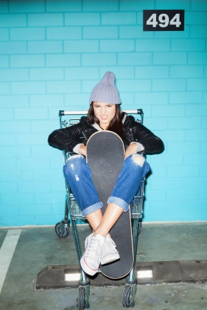 Young pretty woman in beanie holding skateboard  over blue brick wall. Naughty girl having fun in shopping cart. Indoors, lifestyle photo