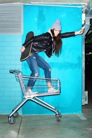 rowdy: Mujer joven inconformista cobarde pie con helado y skateboard en carrito de la compra sobre la pared de ladrillo azul. Naughty girl having fun. Interior, el estilo de vida
