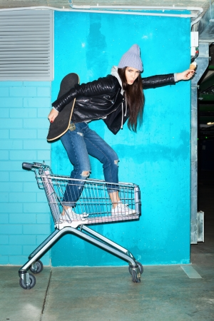 Young funky hipster woman standing with ice cream and skateboard in shopping cart over blue brick wall. Naughty girl having fun . Indoors, lifestyle photo