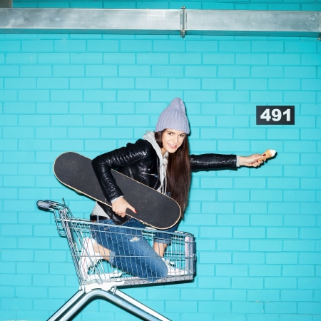 Young funky hipster woman with ice cream and skateboard sitting in shopping cart over blue brick wall. Naughty girl having fun . Indoors, lifestyle photo