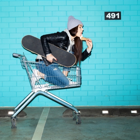 Young trendy woman with skateboard eating ice cream in shopping cart over blue brick wall. Naughty girl having fun . Indoors, lifestyle photo