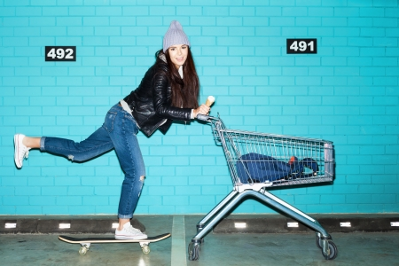 Young funky hipster woman riding skateboard in front pushing shopping cart over blue brick wall. Naughty girl having fun . Indoors, lifestyle photo