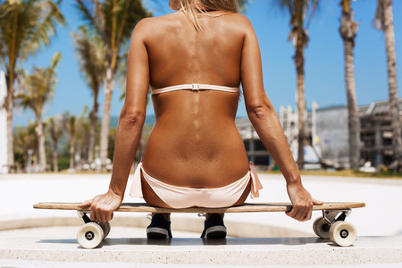 longboard: Beautiful young girl sitting on longboard in day. Skateboarding. Outdoors, lifestyle