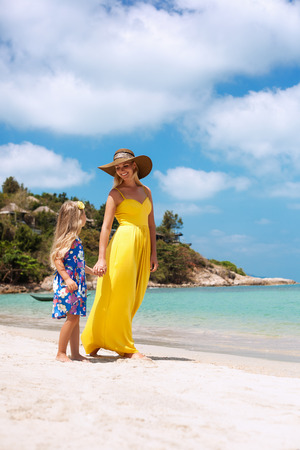 yelloow: Beautiful little daughter and her mother have  a good time at the seaside resort. Outdoors Stock Photo