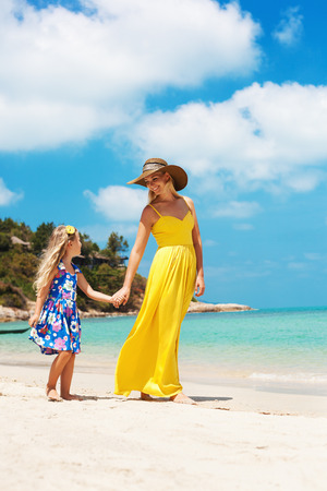 yelloow: little girl and her mother walking at the seaside resort. Outdoors