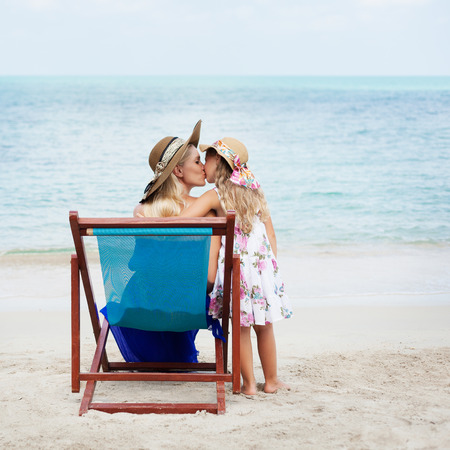 beach kiss: Little girl kissing her mother sitting in a chair on the beach. Outdoors
