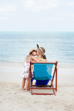 beach kiss: Beautiful little girl kissing her young mother sitting in a chair on the beach. Outdoors