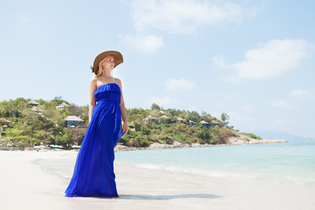 sexy party girl: Young blonde woman wearing straw hat and elegant dress posing standing on beach looking away at the sea. Outdoors Stock Photo