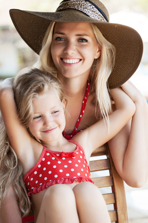 little blonde girl: Little girl hugging her mother in a tropical cafe. Outdoors.