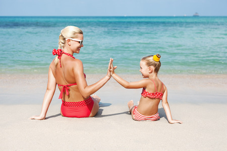 Young happy mother with little girl and daughter giving five at sea beach in summer. Outdoors