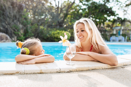 Little girl and her mother with cocktail in tropical beach pool  Outdoors photo