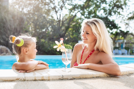 pool party: Little pretty girl and her beautiful mother with cocktail in tropical beach pool