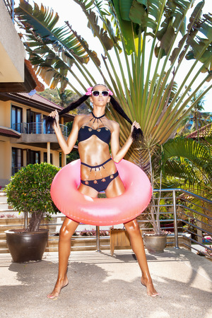 Young woman in white sunglasses with pink inner tube pulls her hair in different directions for the two arms of the tail at tropical resort in summer day. Outdoors photo