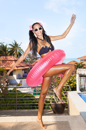 Young woman in white sunglasses with pink inner tube walking at tropical resort in summer day. Outdoors photo