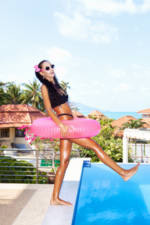 Young woman in white sunglasses with pink inner tube having fun at tropical resort in summer day. Outdoors photo