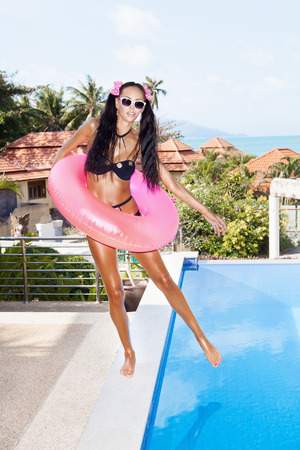 Young woman in white sunglasses with pink inner tube having fun near pool at tropical resort in summer day. Outdoors photo
