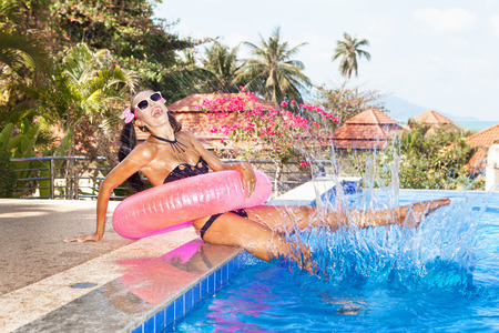 Young woman in bikini and white sunglasses with pink inner tube having fun near pool. Outdoors photo