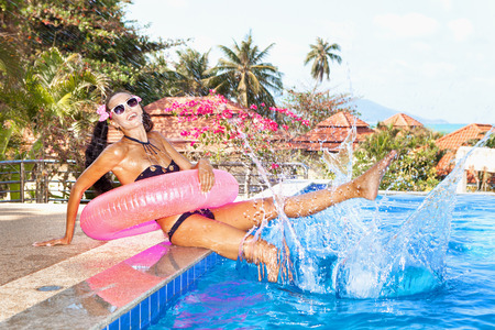 Young woman in bikini with pink inner tube having fun near pool at tropical resort in summer day. Outdoors photo