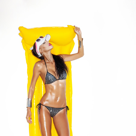 Beauty woman in bikini in suntan oil with yellow float posing near white wall. Not isolated. Lifestyle, outdoors
