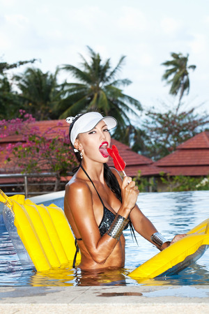 sucking lollipop: Young woman with beauty tanned body sitting on yellow air mattress in the pool in summer sucking lollipop and having fun . Outdoor fashion portrait of happy girl in white hat