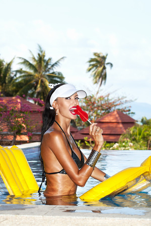 tanned body: Young woman with beauty tanned body sitting on yellow air mattress in the pool in summer licking lollipop . Outdoor fashion portrait of happy girl in white hat