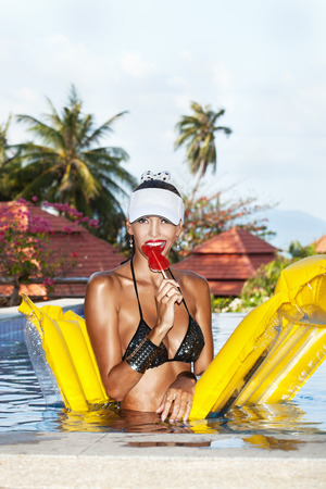 tanned body: Young woman with beauty tanned body sitting on yellow air mattress in the pool in summer and licking  red lollipop . Outdoor fashion portrait of happy girl in white hat