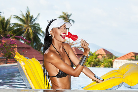 sexy lollipop: Woman with beauty tanned body sitting on yellow air mattress in the pool in summer and having fun . Outdoor fashion portrait of happy girl in white hat Stock Photo
