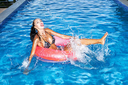 Woman floating in an inner tube in a swimming pool and laughing. Outdoor portrait of girl having fun. photo