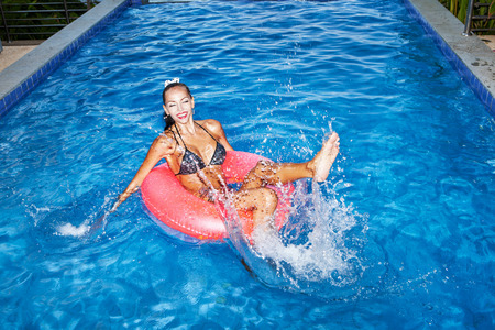 flesh: naughty girl floating in an pink inner tube in a swimming pool and laughing. Outdoor portrait of girl having fun.
