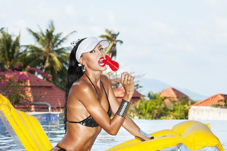tanned body: Young sexy woman with beauty tanned body sitting on yellow air mattress in the pool in summer and licking lollipop . Outdoor fashion portrait of happy girl in white hat Stock Photo
