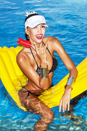 tanned body: Woman with tanned body sitting on yellow air mattress in the pool in summer and licking lollipop . Outdoor fashion portrait of happy girl in white hat Stock Photo