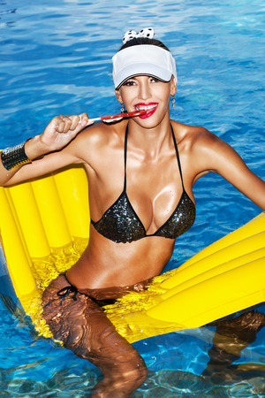 tanned body: Woman with tanned body sitting on yellow air mattress in the pool in summer and licking lollipop . Outdoor fashion portrait of happy girl having fun