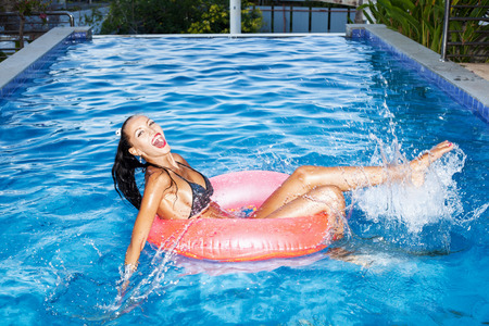 float tube: Young woman floating in an pink inner tube in a swimming pool and laughing. Outdoor portrait of girl having fun.