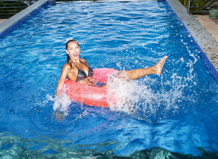 schwimmring: Junge Frau glücklich schwebend in einem inneren Rohr in einem Schwimmbad und lachen. Outdoor-Porträt der frechen Mädchen Spaß.