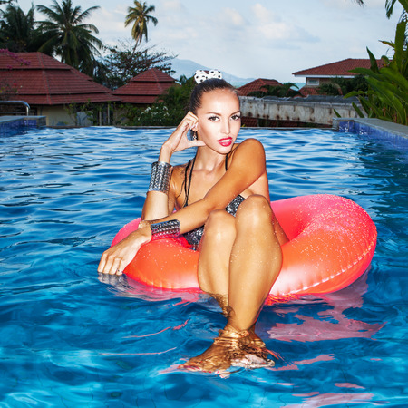 Sexual young woman floating in an inner tube in a swimming pool. Outdoors, lifestyle photo