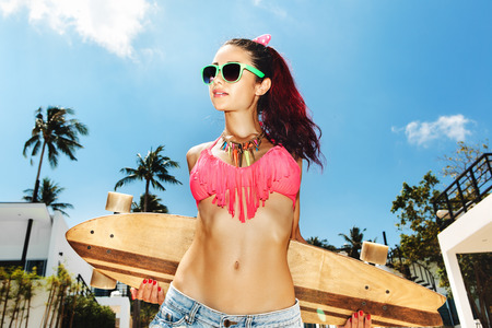 Girl in sunglasses holding  longboard on background at tropical sky. Lifestyle outdoor portrait.