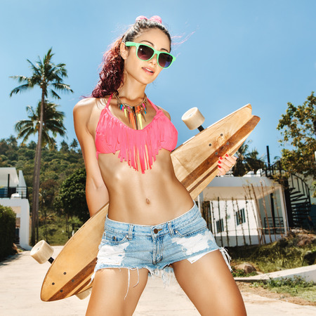 longboard: Pretty girl in sunglasses with skateboard posing on background at tropical sky  Lifestyle outdoor portrait