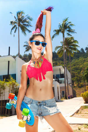 Trendy young woman witn red hair in sunglasses having fun with longboard  Lifestyle outdoor portrait  photo