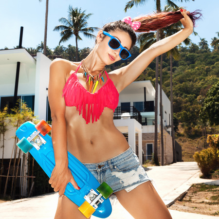 longboard: Trendy young woman witn red hair in sunglasses having fun with longboard. Lifestyle outdoor portrait. Stock Photo