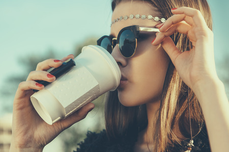 casual fashion: Beautiful hipster woman in sunglasses drink  coffee  Close-up lifestyle outdoor portrait