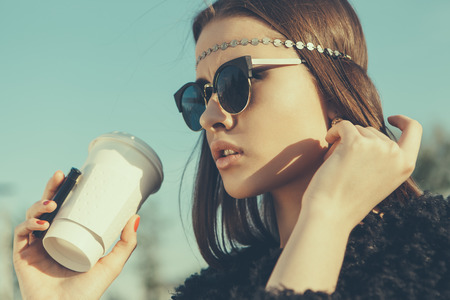 Hipster girl in sunglasses with cup of coffee  Close-up lifestyle outdoor portrait Standard-Bild