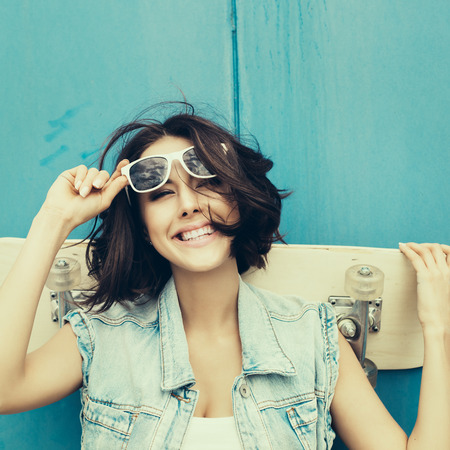 Young happy girl in sunglasses posing with skateboard. Lifestyle outdoor toned portrait photo