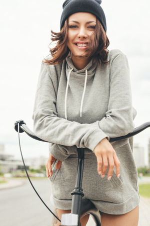 Young hipster girl with black bike looking at camera and smiling. Outdoor lifestyle portrait