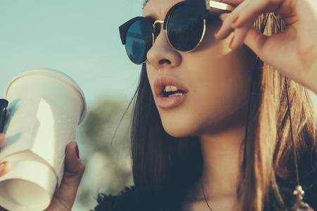 ライフスタイル: 一杯のコーヒーとサングラスでかなり内気な少女。クローズ アップのライフ スタイル屋外のポートレート