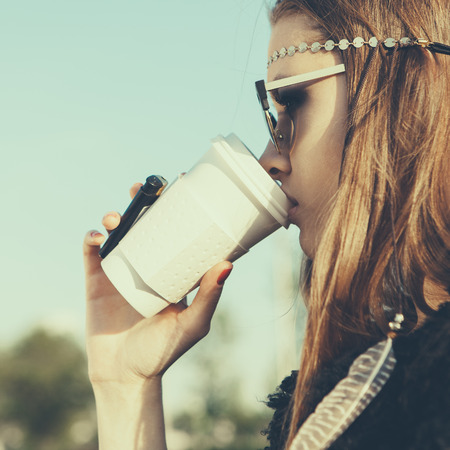 Hipster girl in sunglasses with drink coffee. Close-up lifestyle outdoor portrait photo